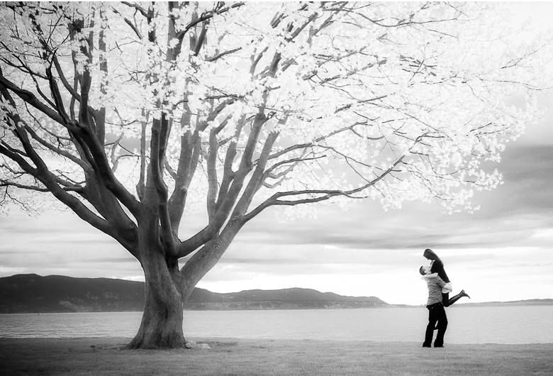 artsy engagement session picture with tree and ocean in the background infrared effect Missy and Chase romp on the beach